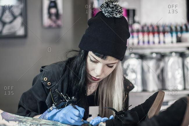 Female tattoo artist tattooing a leg