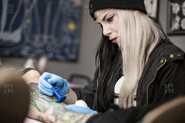 Female tattoo artist shaving leg before tattooing