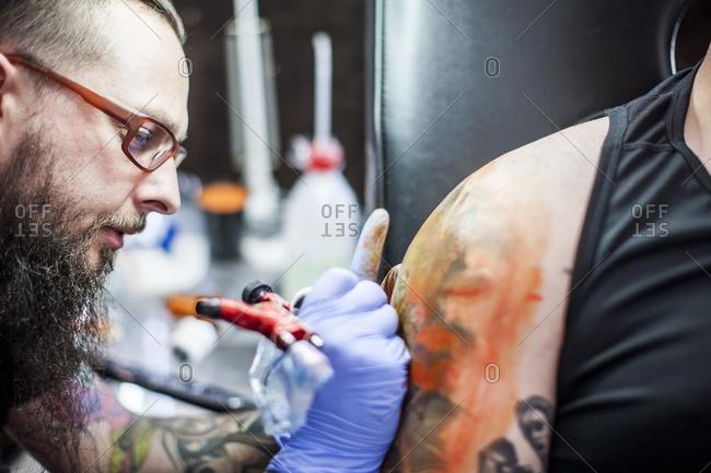 Tattoo artist tattooing an arm