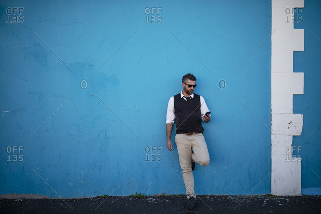 Man leaning against blue wall looking on cell phone