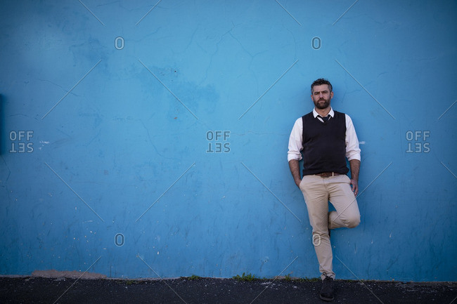 Man leaning against blue wall