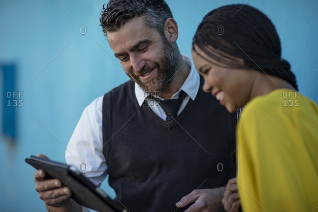 Smiling man and woman looking at tablet together