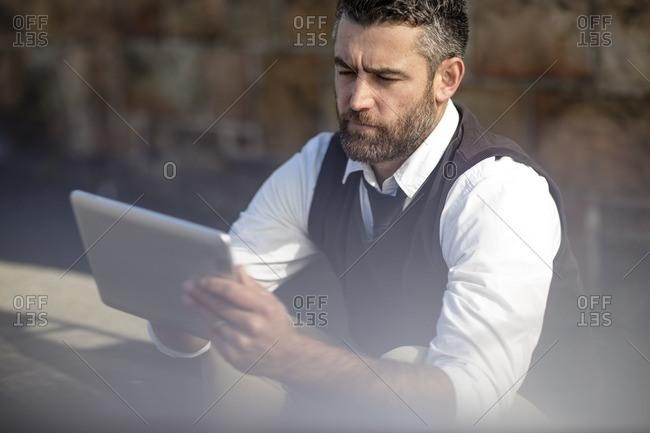 Man looking at tablet outdoors