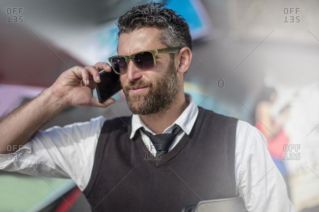 Smiling man wearing sunglasses talking on cell phone