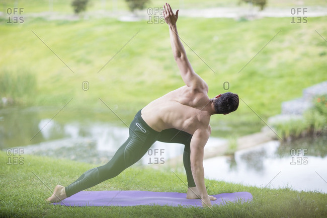 Young man practicing yoga in park