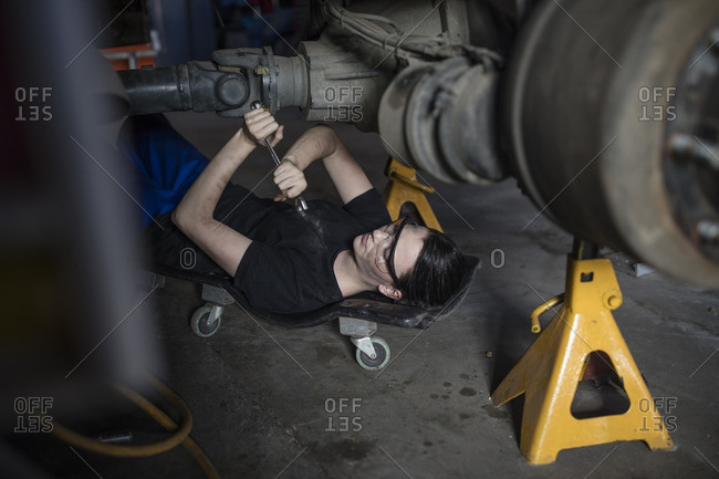 Female mechanic working at fire brigade workshop- lying on creeper