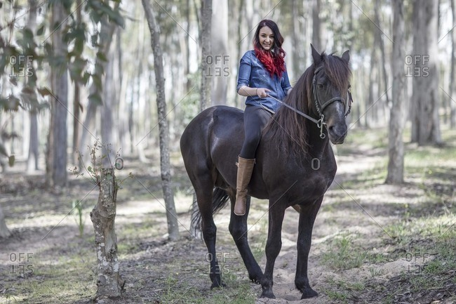Smiling young woman on horse in forest