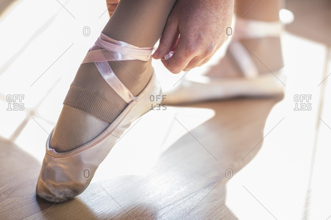 Ballet dancer putting shoes on