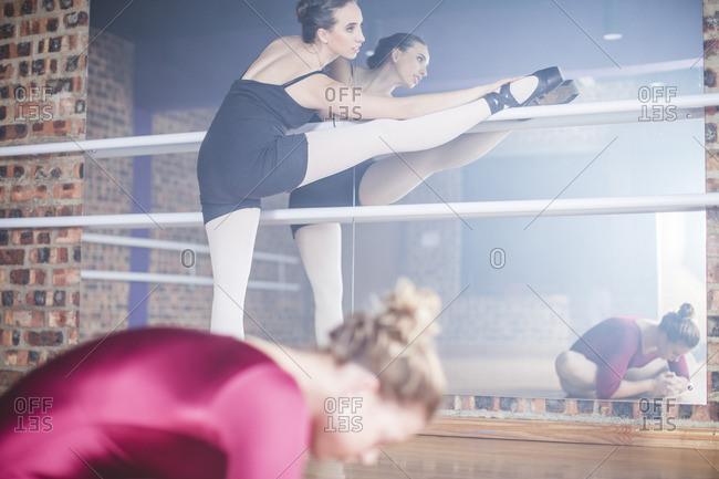 Ballet dancer stretching leg at studio
