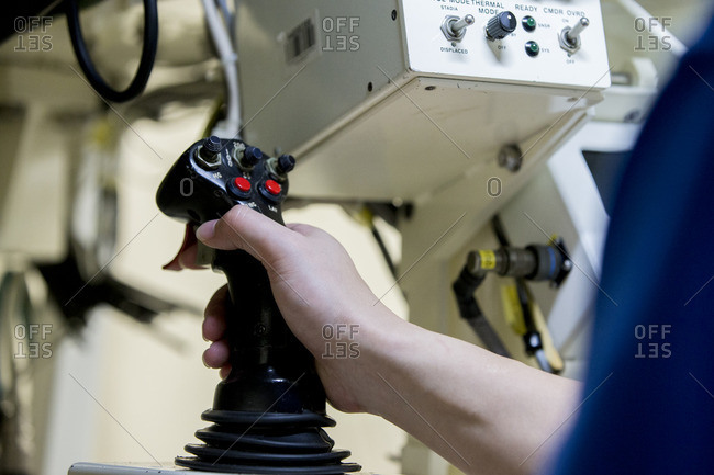 Man's hand on the control stick in aircraft cockpit