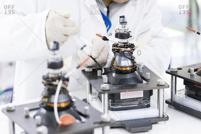 Technician working on a mechanical device in lab