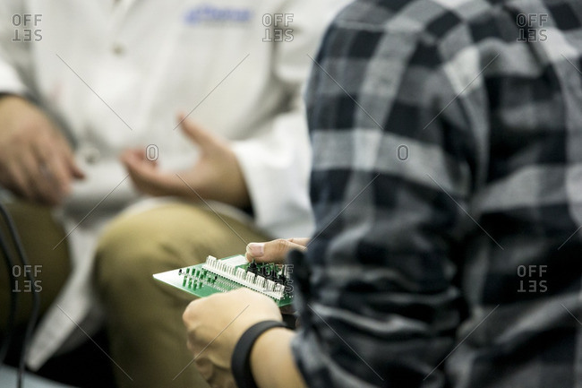 Person holding a circuit board with switches on it