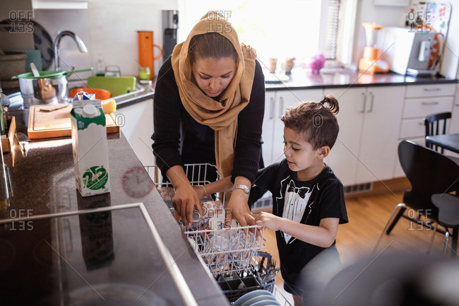 Mother and son arranging utensils in dishwasher at kitchen