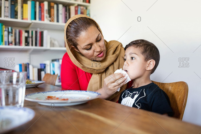 Mother wiping son's mouth after lunch at dining table