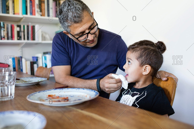 Father wiping son's mouth after lunch at dining table