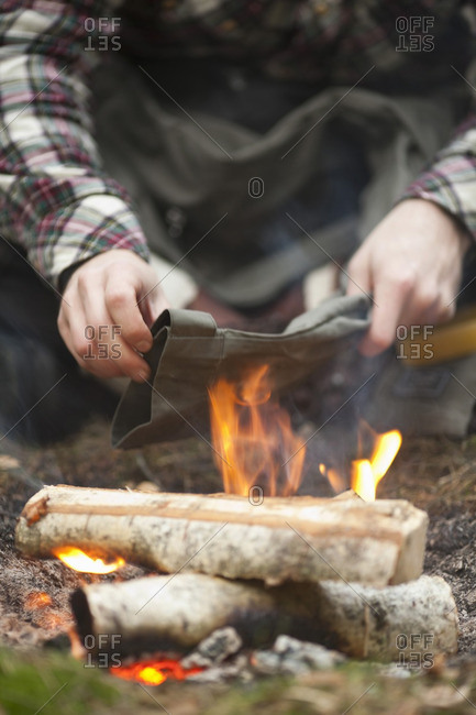 Midsection of man heating pant over bonfire after applying beeswax at campsite