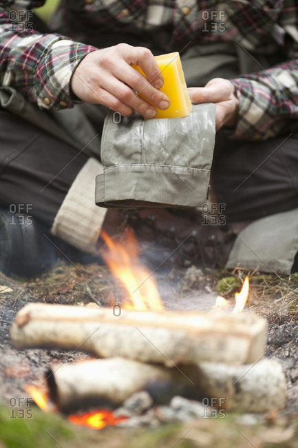 Low section of man rubbing beeswax on pant by campfire