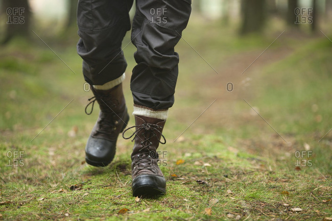 Low section of hiker walking in forest