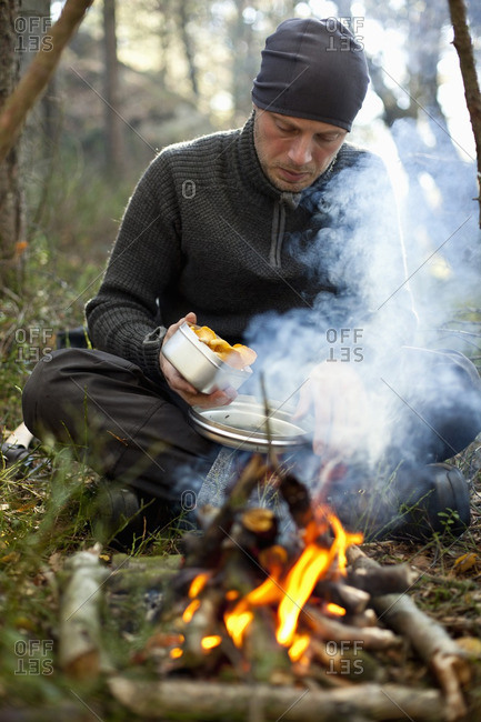 Man cooking chanterelle mushrooms at bonfire in forest