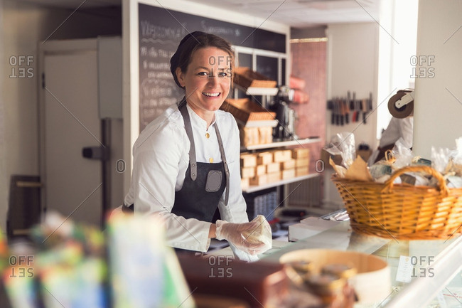 Portrait of happy female owner working at display cabinet in grocery store
