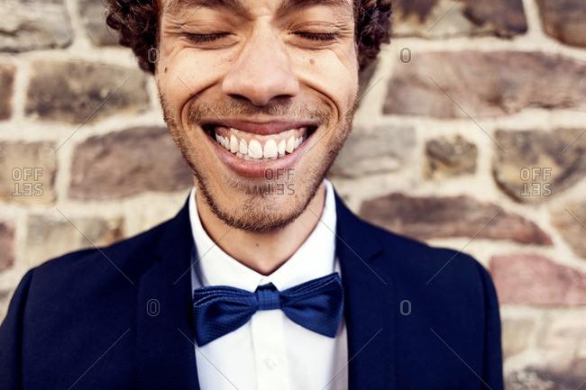 Happy gay man against brick wall