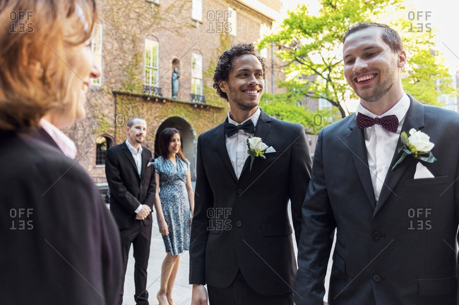 Happy gay couple standing in front of priest with guest in background during wedding ceremony