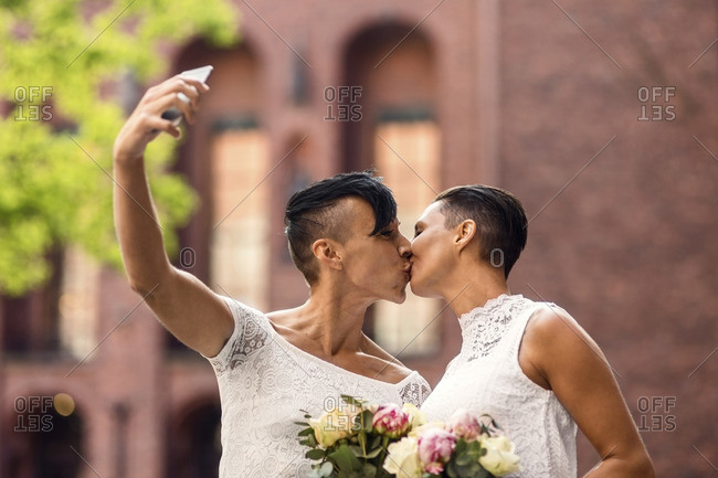 Lesbian couple taking selfie from mobile phone while kissing