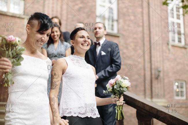 Low angle view of happy lesbian couple on staircase with guests in background