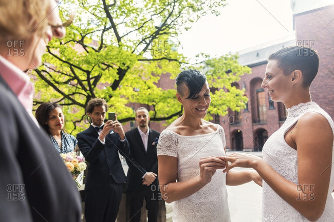Happy lesbian women exchanging rings during wedding ceremony