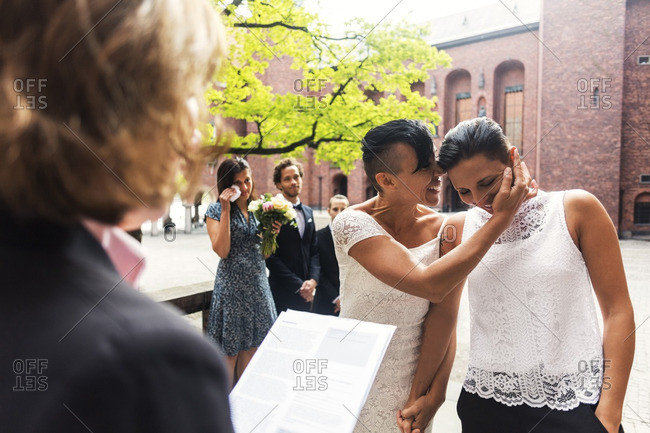 Guests and priest looking cheerful lesbian couple whispering during wedding ceremony