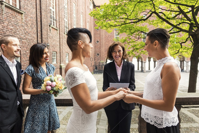 Priest and guests looking at happy lesbian couple holding hands during wedding ceremony