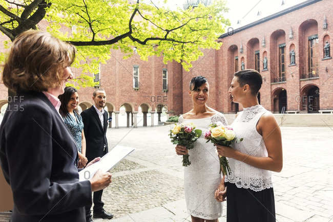 Civil wedding stock photos offset happy lesbian couple standing in front of female priest for wedding ceremony junglespirit Gallery