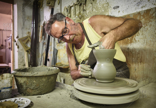 Potter in workshop working on earthenware jug