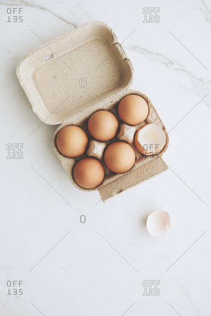 Half a dozen eggs in a carton with one cracked
