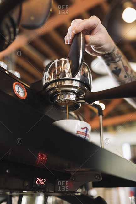 Hand pouring coffee from machine
