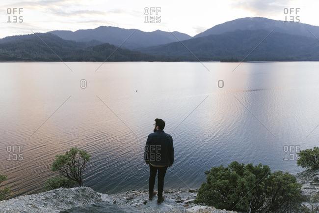 Man overlooking tranquil rural lake