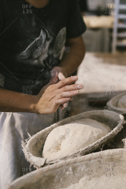 Baker by bread dough in basket