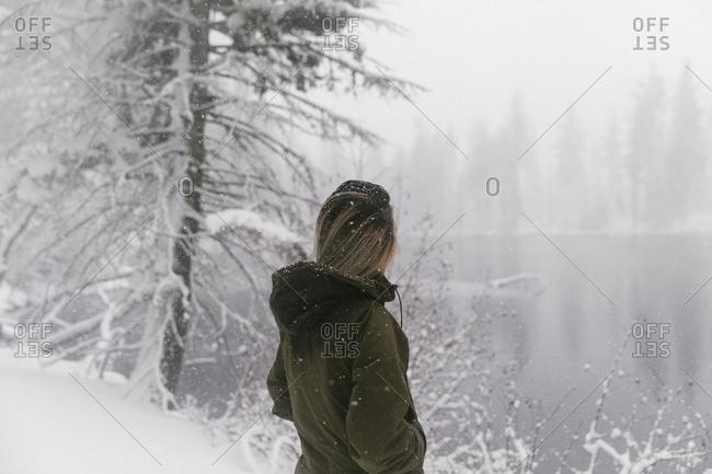 Woman at edge of snowy rural lake