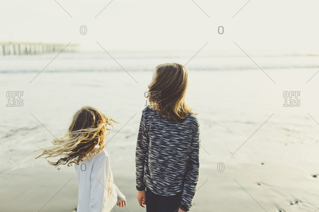 Two young girls with windblown hair on beach