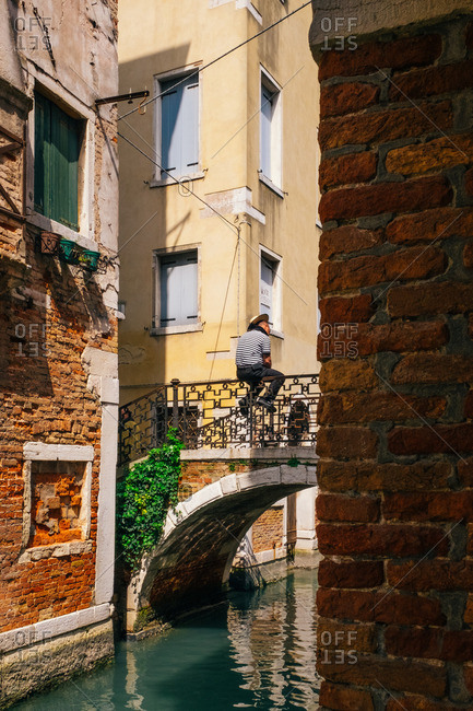 Venice, Italy - April 11, 2016: A gondolier sits on a bridge in Venice, Italy