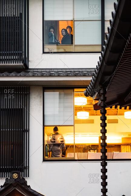 Asakusa, Japan - November 19, 2016: Family and waitress in windows in Asakusa, Japan