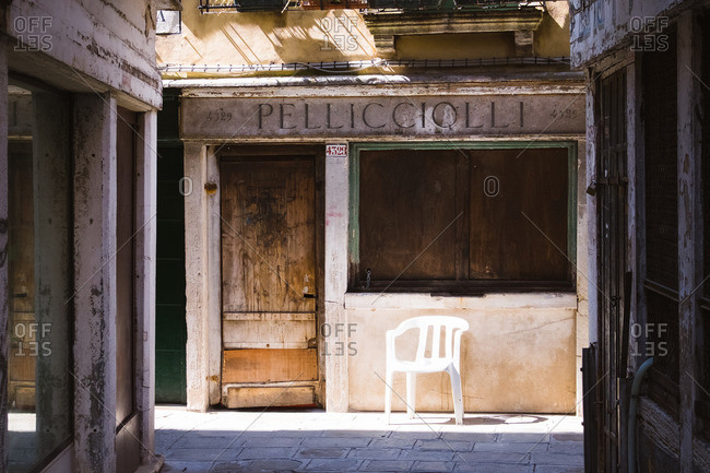 Venice, Italy - April 11, 2016: A plastic chair by old storefront, Venice, Italy