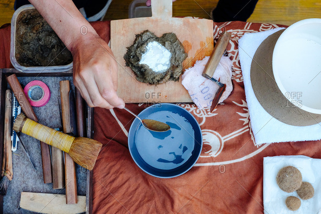 A craftsman mixing clay for pottery