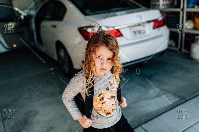 Young girl with backpack in garage