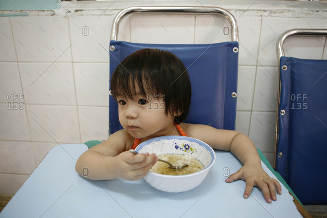 Ho Chi Minh City, Vietnam - March 11, 2009: Little girl eating soup in an orphanage