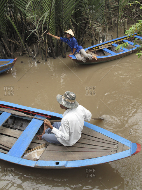 Vietnam - March 13, 2009: Men in traditional wooden long boats in the Mekong Delta