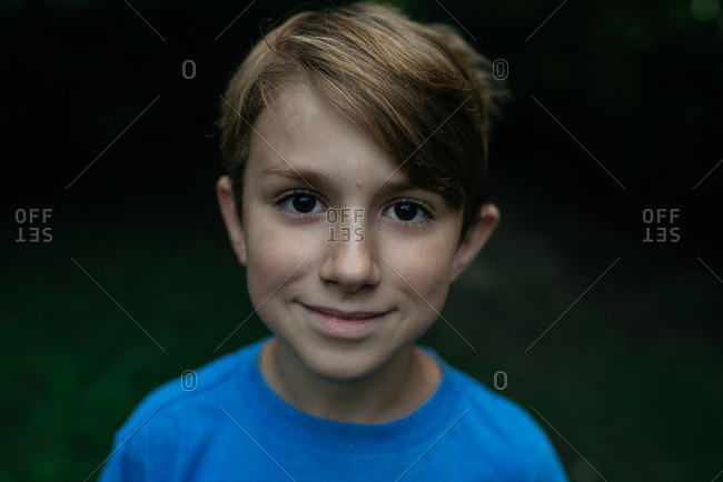 Boy in T-shirt outdoors with dark background