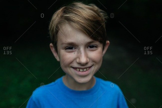 Grinning boy in T-shirt outdoors