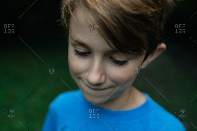 A boy outdoors in T-shirt looking down