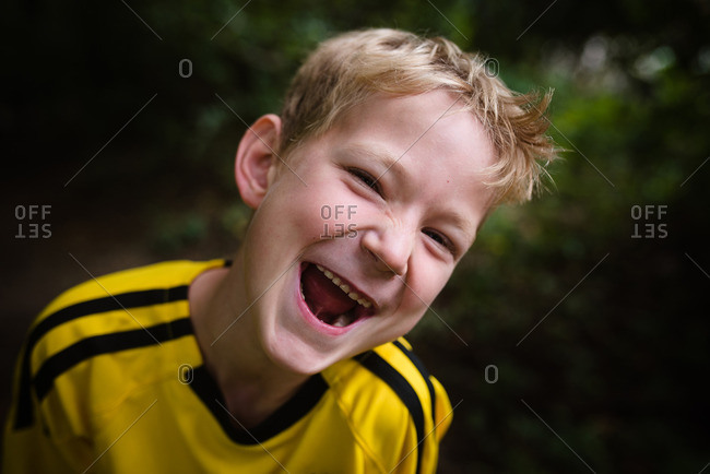 Laughing blonde boy outside in soccer jersey